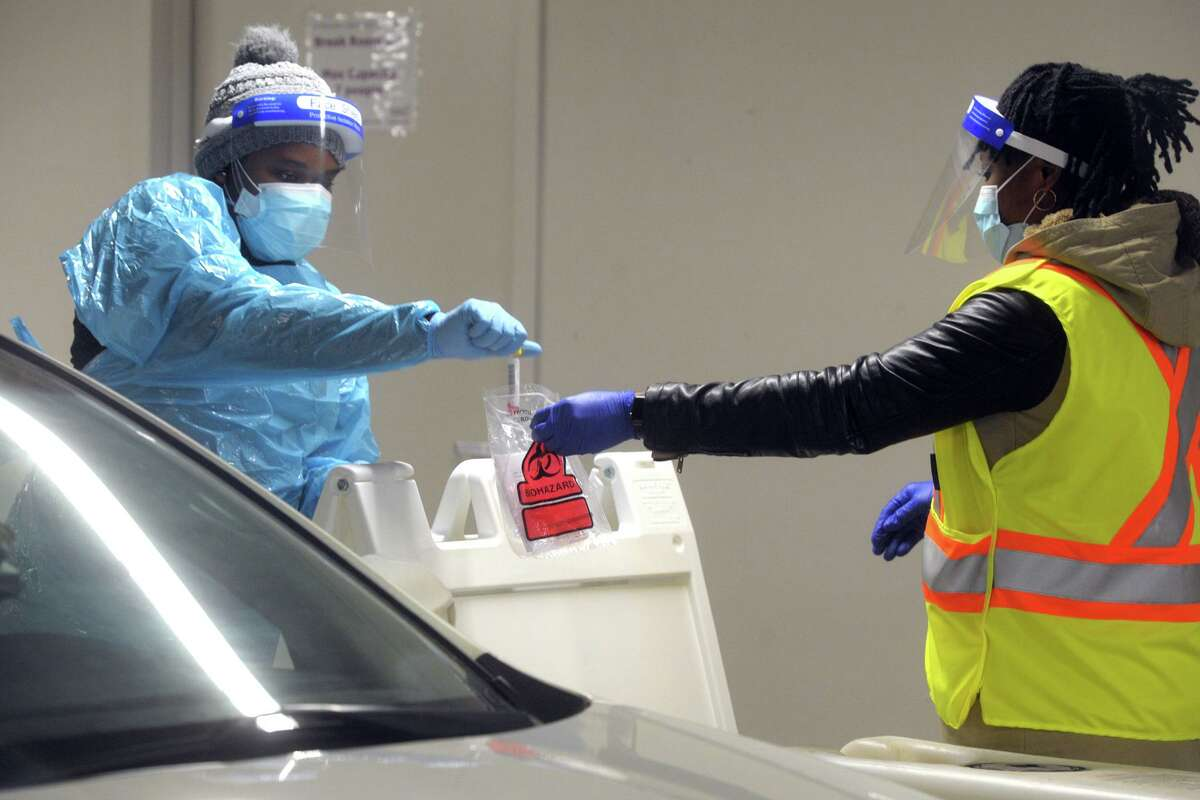Medical personnel work in Hartford HealthCare's new drive-through COVID-19 testing sight inside the parking garage adjacent to the Arena at Harbor Yard, in Bridgeport, Conn. Jan. 25, 2021.