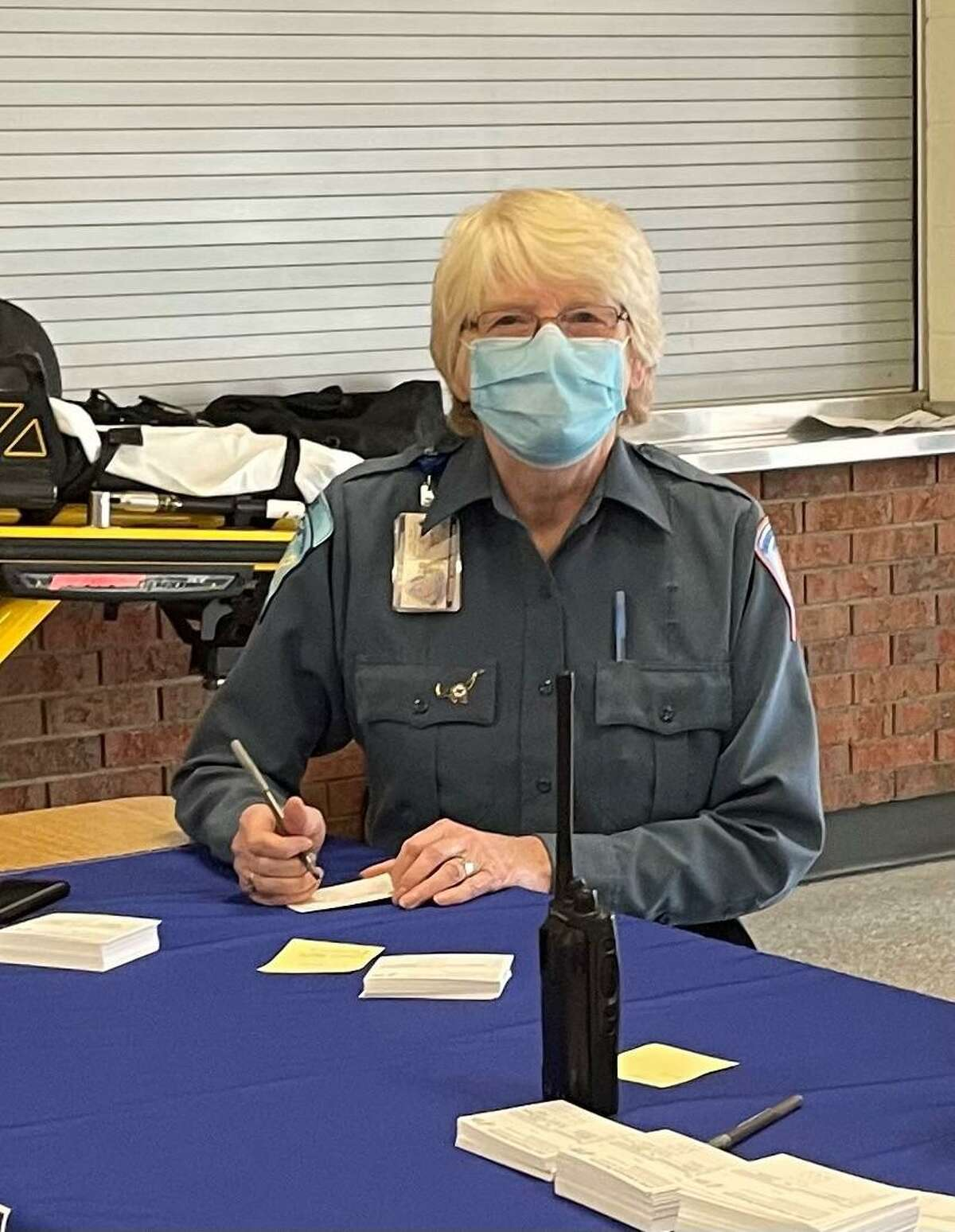Trumbull EMS volunteer Barbara Crandall works the registration table at the Jan. 23 vaccination clinic at Trumbull High School.