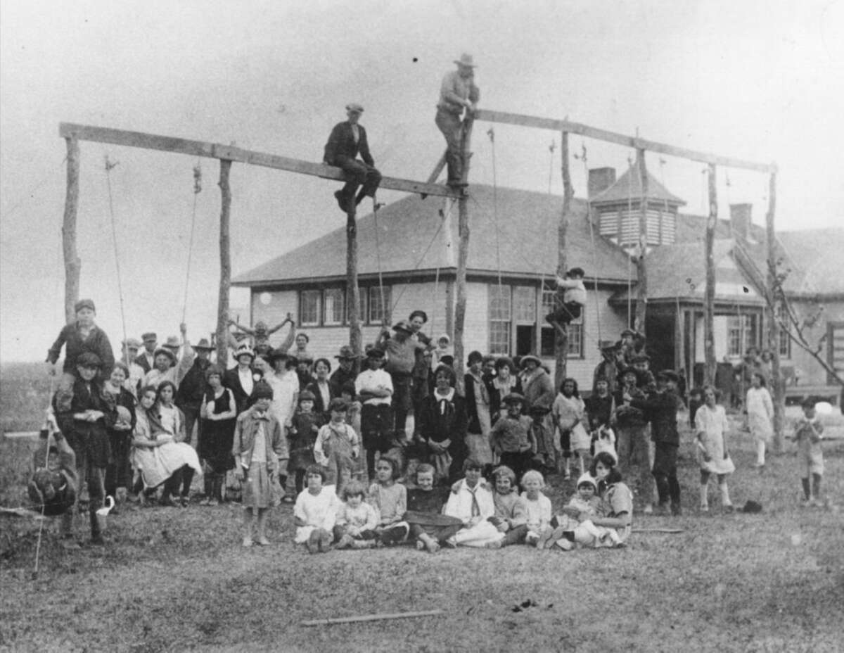 Residents take a break from building a swing set at the Manvel schoolyard in 1922. The women brought food for a picnic while the men worked.