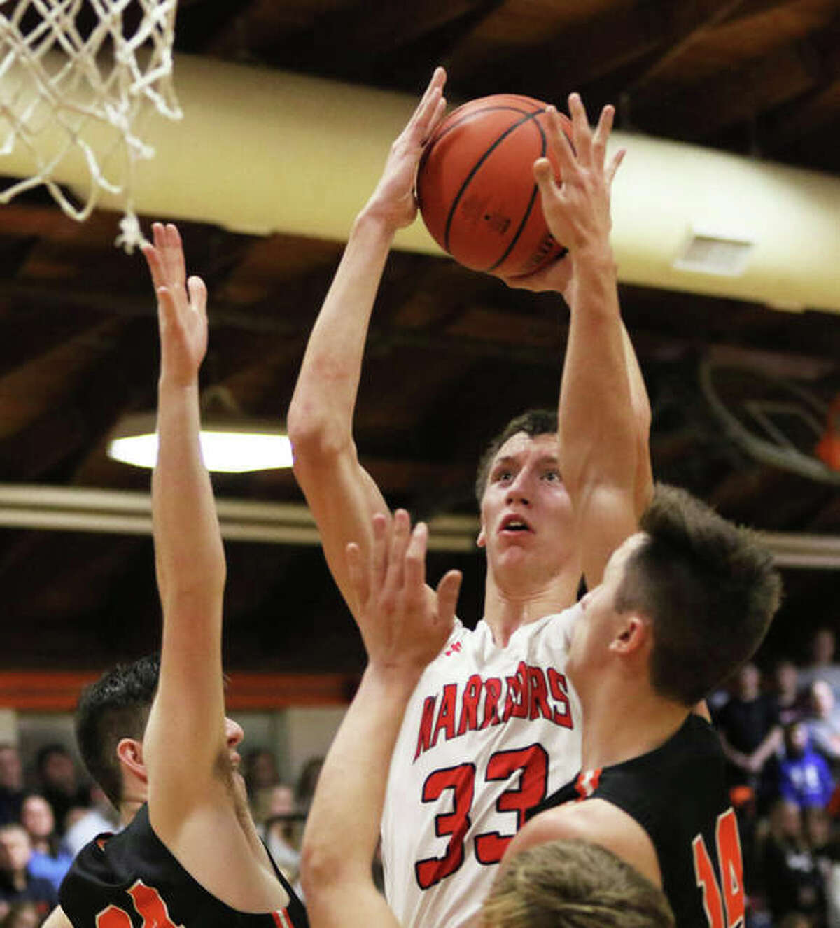Calhoun's Corey Nelson (33) shoots over a pair of Raymond Lincolnwood defenders during the Warriors' victory in a Class 1A regional championship game last season in Raymond.