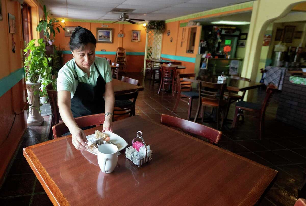 Carmelita's Restaurant owner Carmen Overbay clears a table setting from a lone patron, Friday, March 13, 2020, in Conroe. The restaurant owner said they've had slower traffic due to the new coronavirus, but the 21-year-old establishment plans to remain open as long as they can.