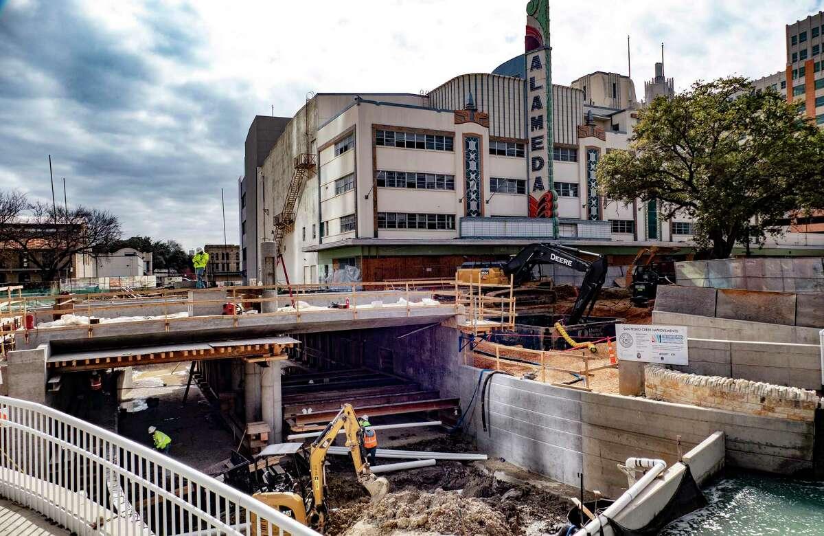 Construction crews work on the bed of San Pedro Creek beneath Houston Street on Monday, Jan. 25, 2021.