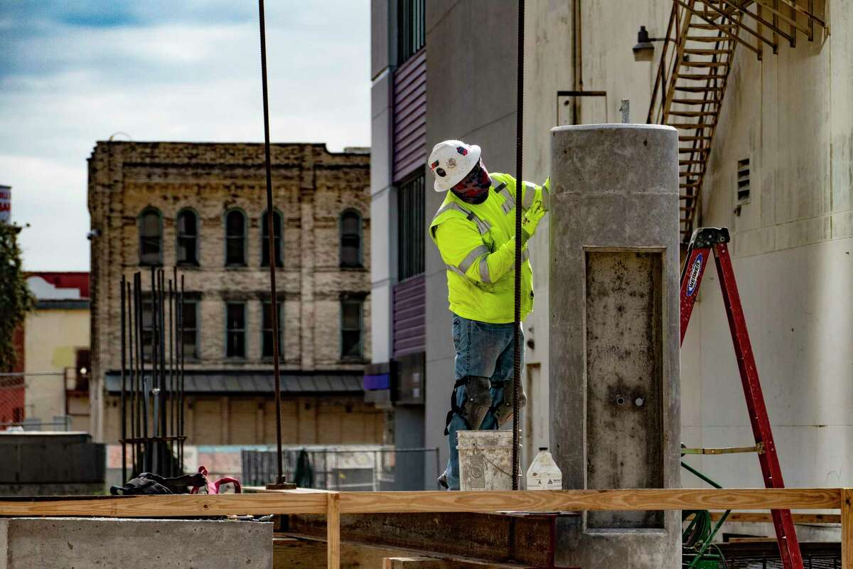 A construction worker gives attention to a pillar on a walkway under construction along Houston Street over San Pedro Creek on Monday, Jan. 25, 2021.