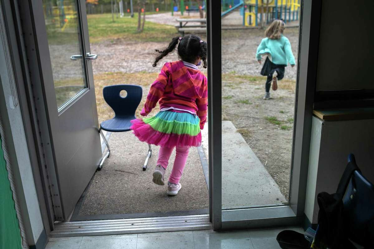 """Kindergarten students race outside for a """"mask break"""" from class at Rogers International School on October 21, 2020 in Stamford, Connecticut."""