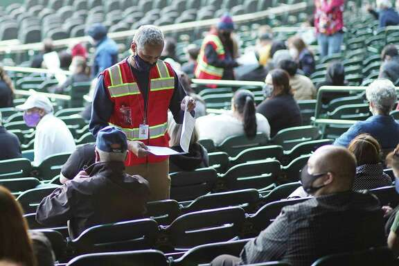 People wait in the bleachers of Minute Maid Park to get their COVID-19 vaccine at a mega site set up Jan. 16 by the City of Houston. Mayor Sylvester Turner said the city will forego mega sites in the future until supply ramps up.