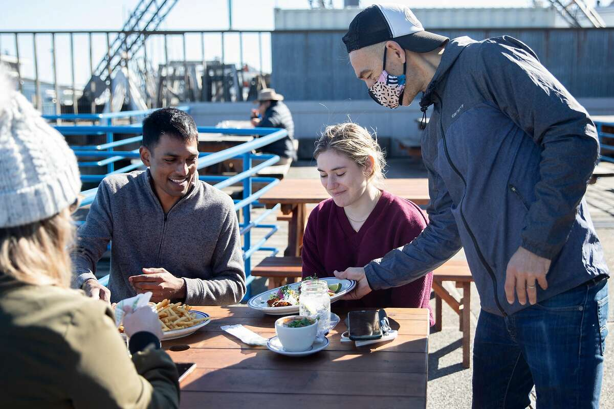 Juan Carlos serves Keshav Saharia of San Francisco (left) and Katie Donick of New York their lunch at the outside patio at Fish restaurant in Sausalito, one of the first places to reopen for outdoor dining after Gov. Gavin Newsom allowed it.