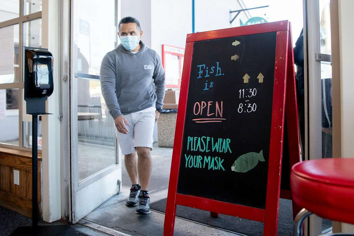 Miguel Batam walks past a sign greeting customers for outdoor dining services at Fish restaurant in Sausalito, Calif. Monday, January 25, 2021. Fish is one of the first restaurants to re-open for outdoor dining after Governor Gavin Newsom lifted shelter-in-place orders. Monday morning, Marin County announced restaurants could open immediately.