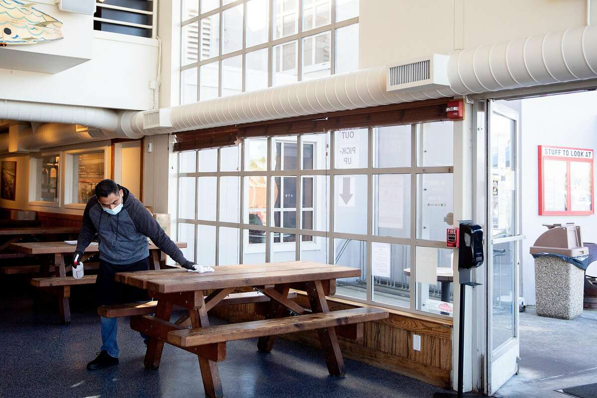 Victor Garcia works to disinfect indoor tables for customers waiting for to-go orders at Fish restaurant in Sausalito. Fish is one of the first restaurants to reopen for outdoor dining after Marin County announced Monday morning that restaurants could open immediately under the governor's new order.