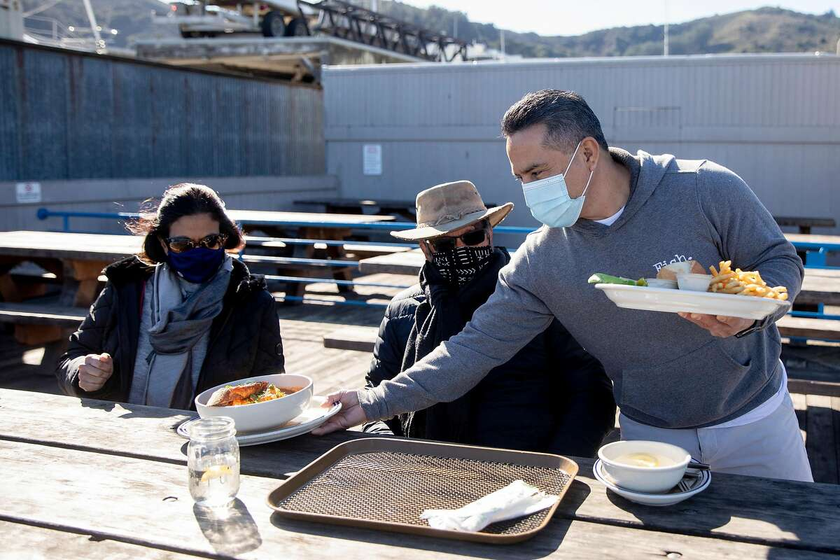 Miguel Batam serves Anoma (left) and Ajith Amerasekera of Berkeley their lunch in the outside patio area at Fish restaurant in Sausalito.