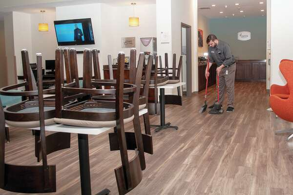 Robert Borga, the on-duty manager at Sleep Inn & Suites in South Jacksonville, cleans the dining area floors Monday.
