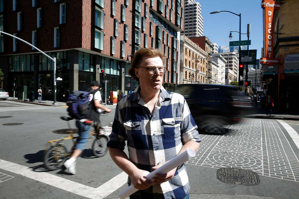 Larry Williamson, neighborhood resident, stands at the intersection of Taylor and Eddy streets as cars drive by behind him, during a tour of the Tenderloin with the Concerned Citizens for Traffic Safety Action Committee.