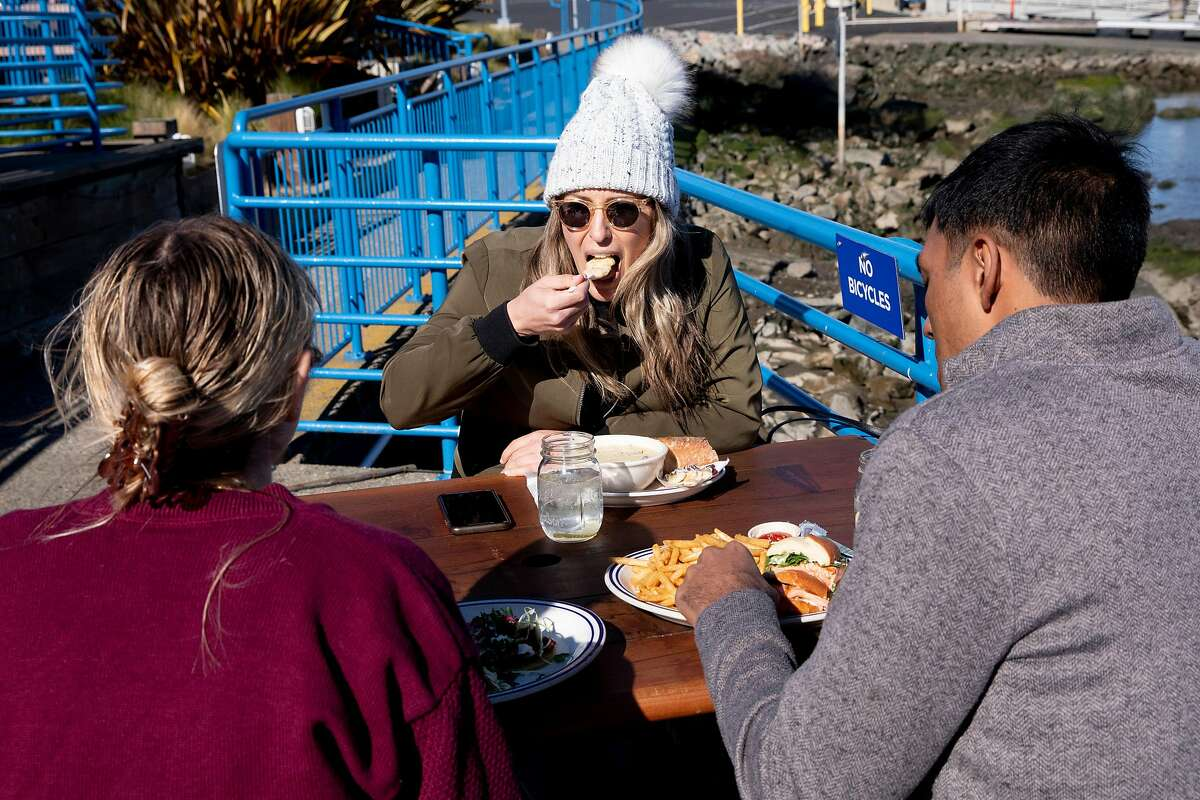 (From left) Katie Donick of New York, Keshav Saharia of San Francisco, and Katie Wilcox of Sausalito enjoy their lunch while seated at the outside patio of Fish restaurant in Sausalito on Jan. 25. Fish is one of the first restaurants to re-open for outdoor dining after Governor Gavin Newsom lifted shelter-in-place orders. Monday morning, Marin County announced restaurants could open immediately.