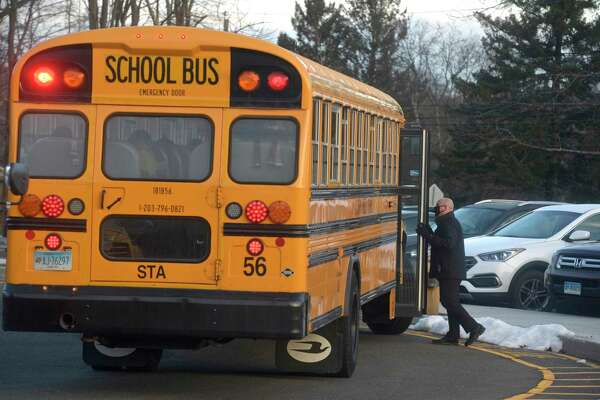 Stadley Rough Elementary School principal Lenny Cerlich welcomes students and their bus driver back to school for the first time since March of last year. Tuesday, January 19, 2021, in Danbury, Conn.