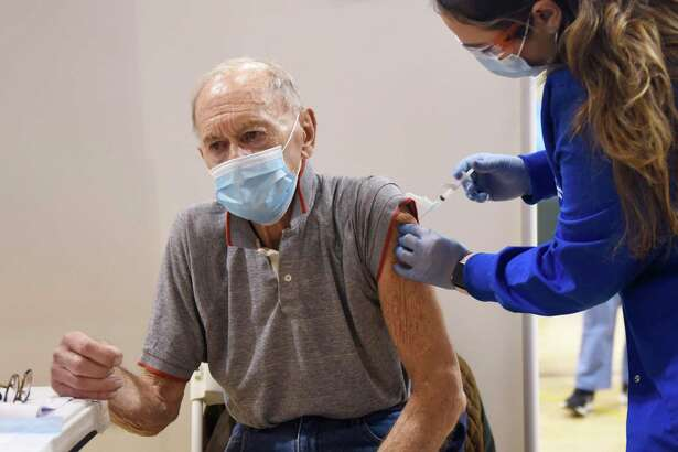 Westport's John Backus, 91, receives the COVID-19 vaccine from nurse Elaine Jara during the Greenwich Hospital COVID-19 vaccine clinic at the Brunswick Lower School Campus in Greenwich on Monday.