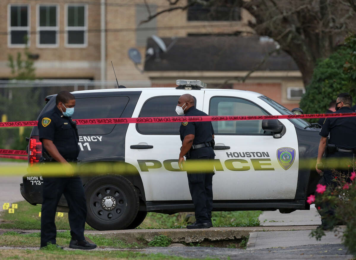 Houston Police officers investigate the scene of an officer-involved shooting on the 100 block of East 44th Street on Monday, Jan. 25, 2021, in Houston. An officer shot a suspected gunman who, unprovoked, fatally shot a 29-year-old man around 2:20 p.m., on the 8500 block of North Main Street.