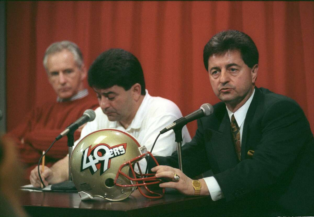 """San Francisco 49ers owner Edward J. DeBartolo, Jr. (left) introduces the new club president, Carmen Policy, to reporters on Feb. 13, 1991. The 49ers also took the opportunity to unveil their new helmet with a new """"49ers"""" logo."""