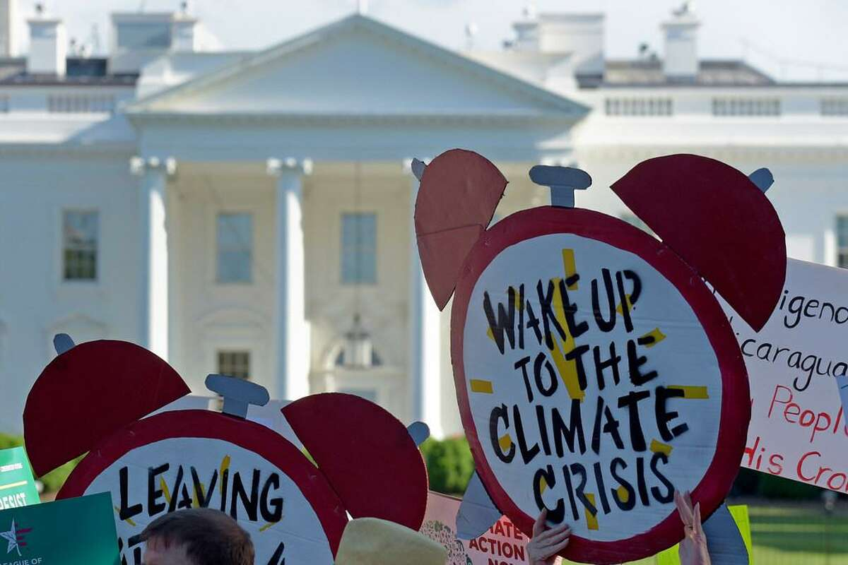In this June 1, 2017 file photo, protesters gather outside the White House in Washington to protest President Donald Trump's decision to withdraw the Unites States from the Paris climate change accord. The Democratic-controlled House has approved legislation that would prevent President Donald Trump from following through on his pledge to withdraw the U.S. from a landmark global climate agreement.
