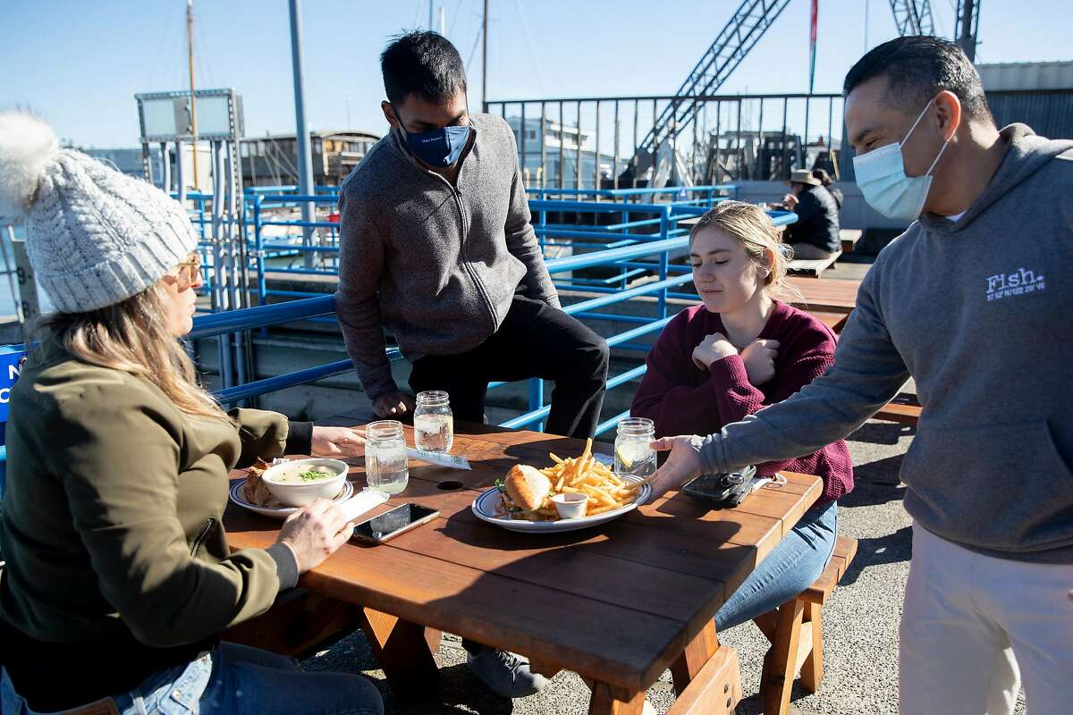 Miguel Batam (right) serves Katie Wilcox (left) of Sausalito, Keshav Saharia of San Francisco and Katie Donick of New York their lunch at Fish restaurant in Sausalito, one of the first restaurants to reopen for outdoor dining after Gov. Gavin Newsom lifted shelter-in-place orders.