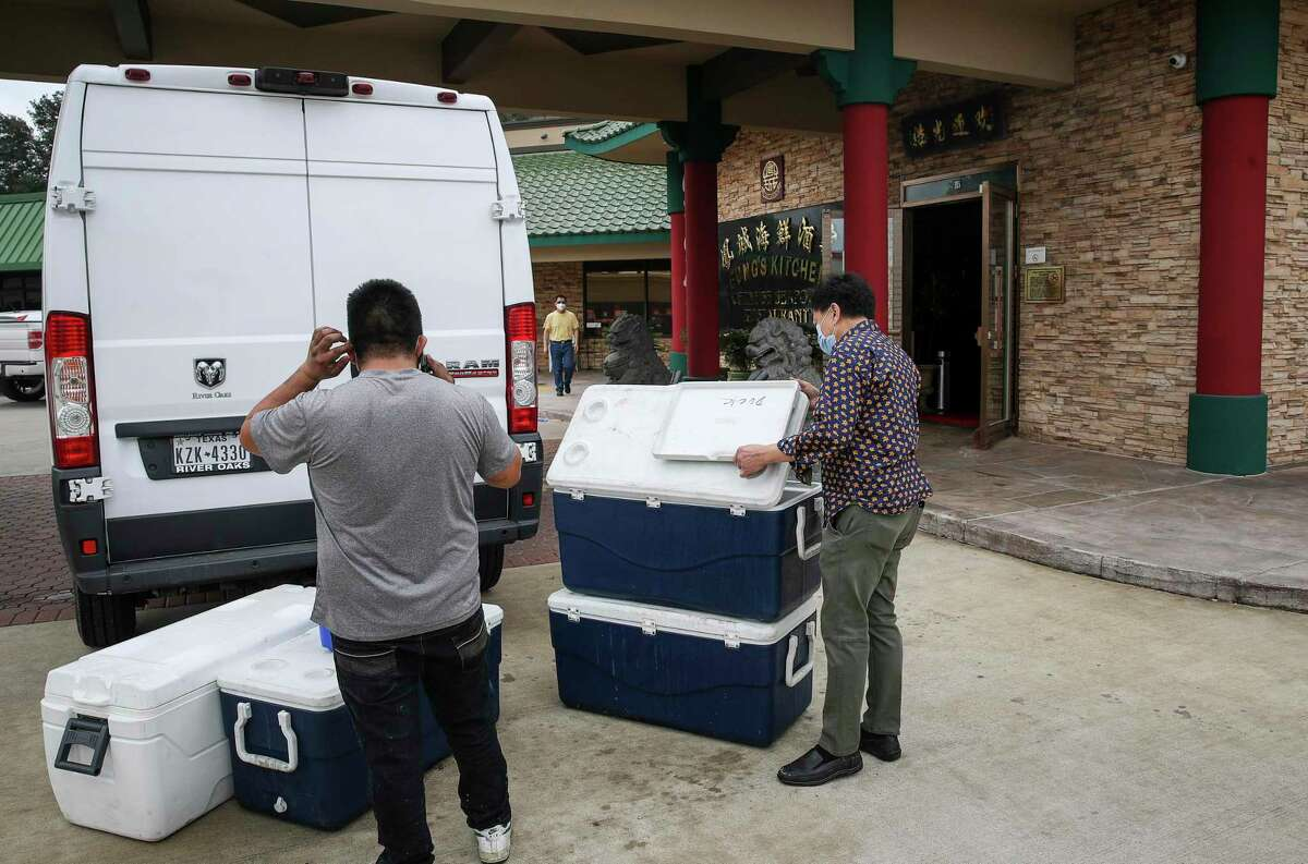 Hoi Fung, right, owner of Fung's Kitchen, and an employee load ruined seafood into a van for disposal Monday, Jan. 25, 2021, at his restaurant in Houston. An overnight fire damaged the restaurant.