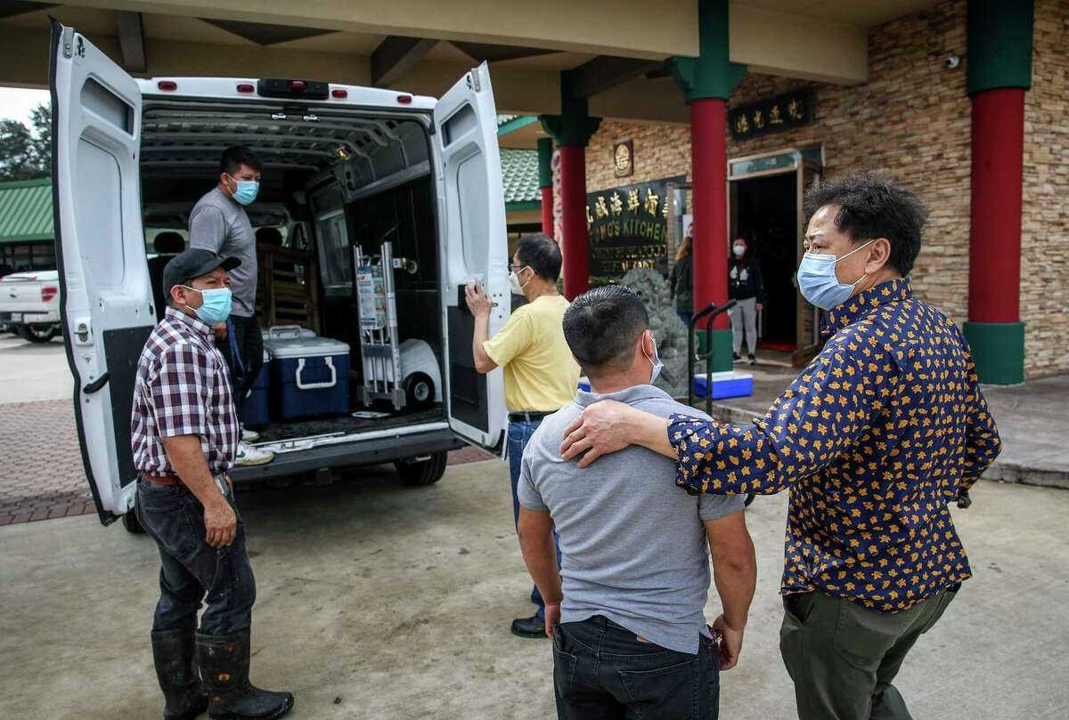 Hoi Fung, right, owner of Fung's Kitchen, comforts an employee as he and other employees load ruined seafood into a van for disposal Monday, Jan. 25, 2021, at his restaurant in Houston. An overnight fire damaged the restaurant.