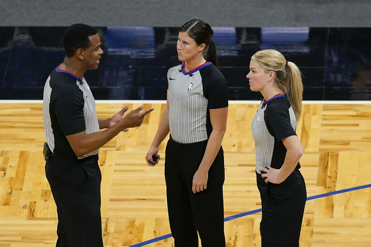 Referees Sean Wright (left), Natalie Sago (center) and Jenna Schroeder chat during a timeout Monday in Orlando, Fla.