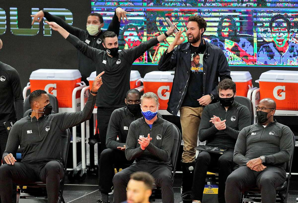 Klay Thompson, standing at right, cheers from the bench after Stephen Curry made a 3-pointer in the first half of the Jan. 25 game against the Timberwolves.