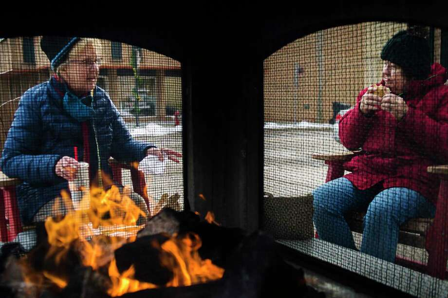 Siobhan Kall, left, and Pat Otterbacher, right, sit down for lunch next to a fireplace in downtown Midland Monday afternoon. (Katy Kildee/kkildee@mdn.net)