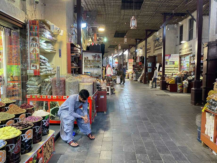 A shopkeeper rests on Saturday in Dubai's empty Old Souk market, where business has decreased amid rising coronavirus cases in the city. Photo: Photo By Katie McQue For The Washington Post. / For The Washington Post