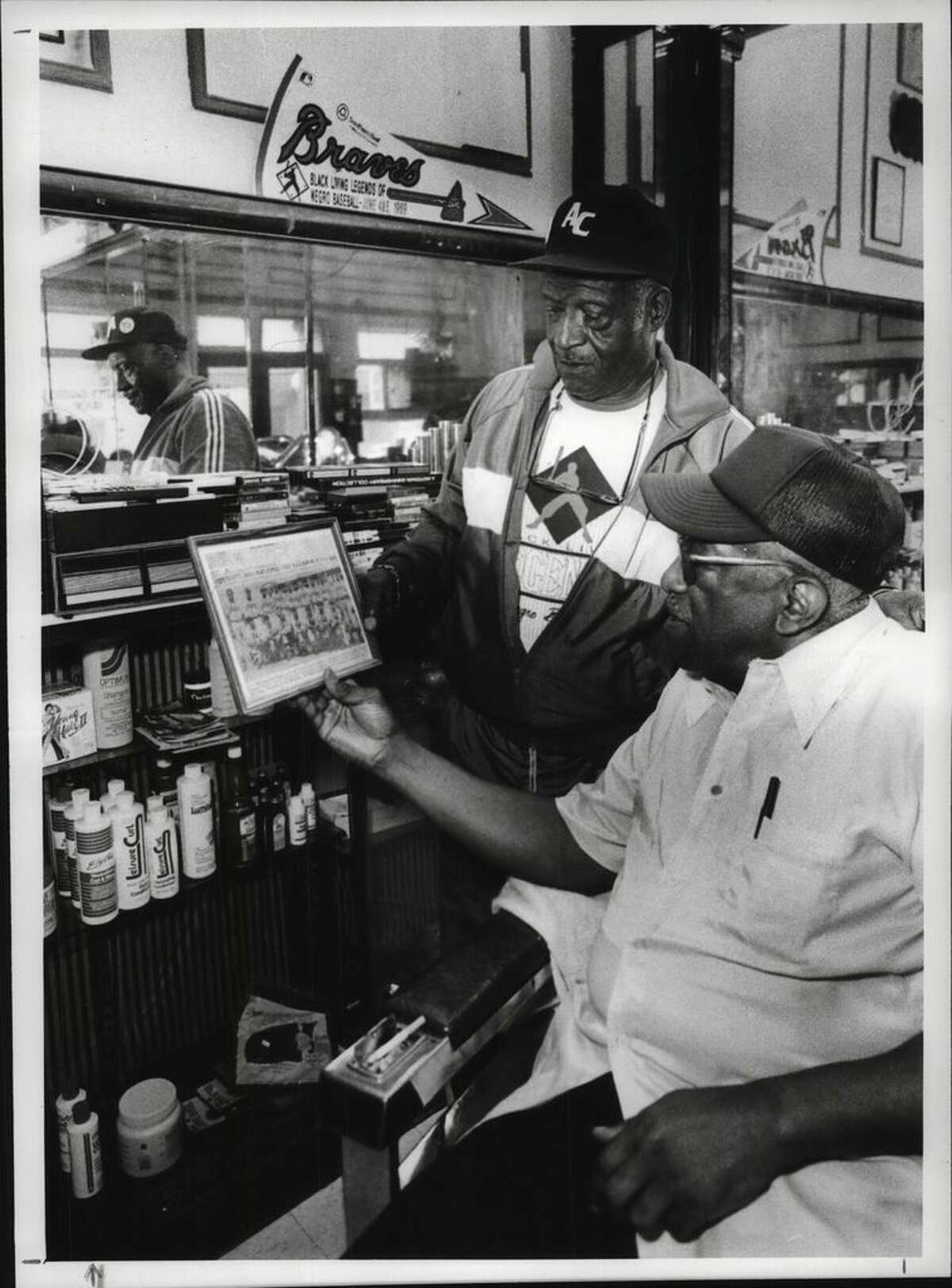 Edsall Walker, standing, shows friend Willie Brand a photograph of the old team, the Homestead Grays on June 21, 1990, at the Wisteria Barber Shop, 323 S. Pearl St. in Albany. (Paul D. Kniskern Sr./Times Union Archive)