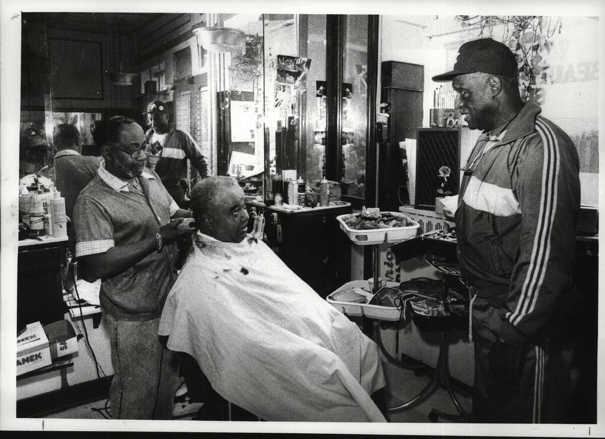 Bob Adkins, owner of the Wisteria Barber Shop at 323 S. Pearl St. in Albany, cuts Ernest Johnson's hair as Edsall Walker visits on June 21, 1990 (Paul Kniskern/Times Union Archive)