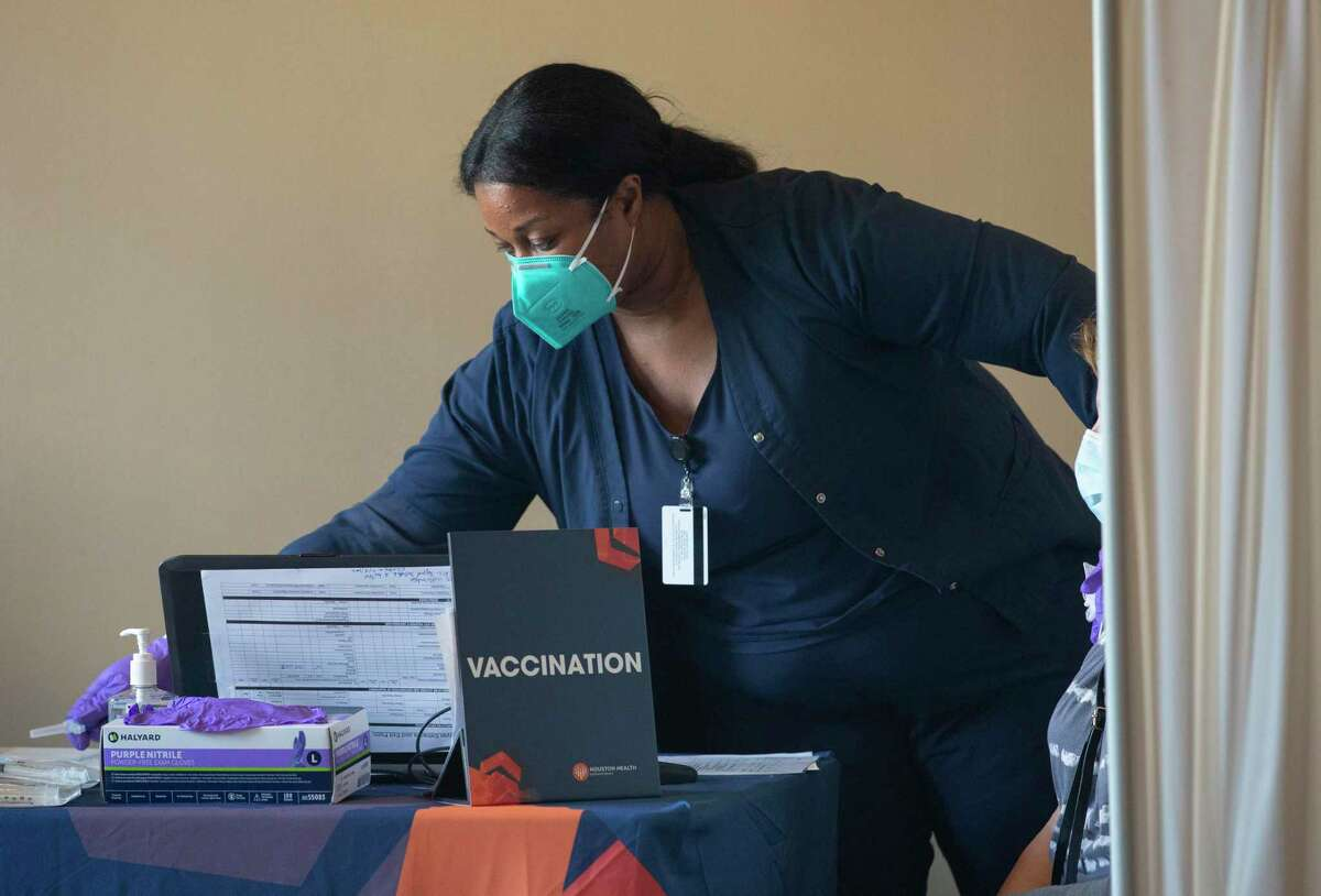 Houston Health Department Licensed Vocational Nurse Francesta Moses prepares to administer a Moderna COVID-19 vaccine to a HHD employee Monday, Dec. 28, 2020, at a Harris Health clinic in Houston. The Houston Health Department received 3,000 doses today.
