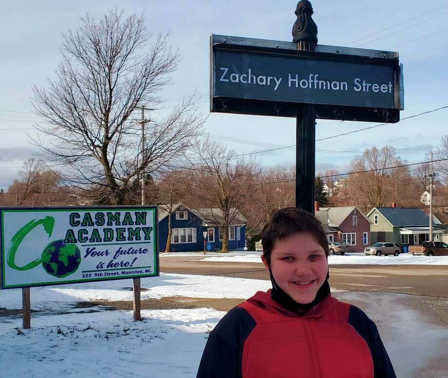Zachary Hoffman,the CASMAN Academy Student of the Month, poses next to the sign that names the school driveway in his honor. (Courtesy photo)