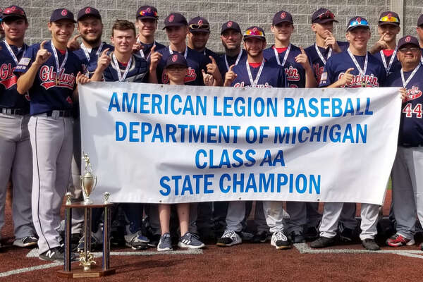 The Gladwin Post 171 baseball team poses with its state championship banner on July 28, 2019.