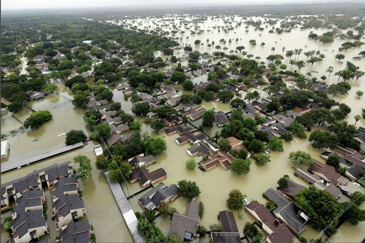 Water from Addicks Reservoir flows into neighborhoods from floodwaters brought on by Hurricane Harvey in 2017. The Federal Housing Finance Agency has put out a call for information about risks that climate change and natural disasters pose to the housing finance system.