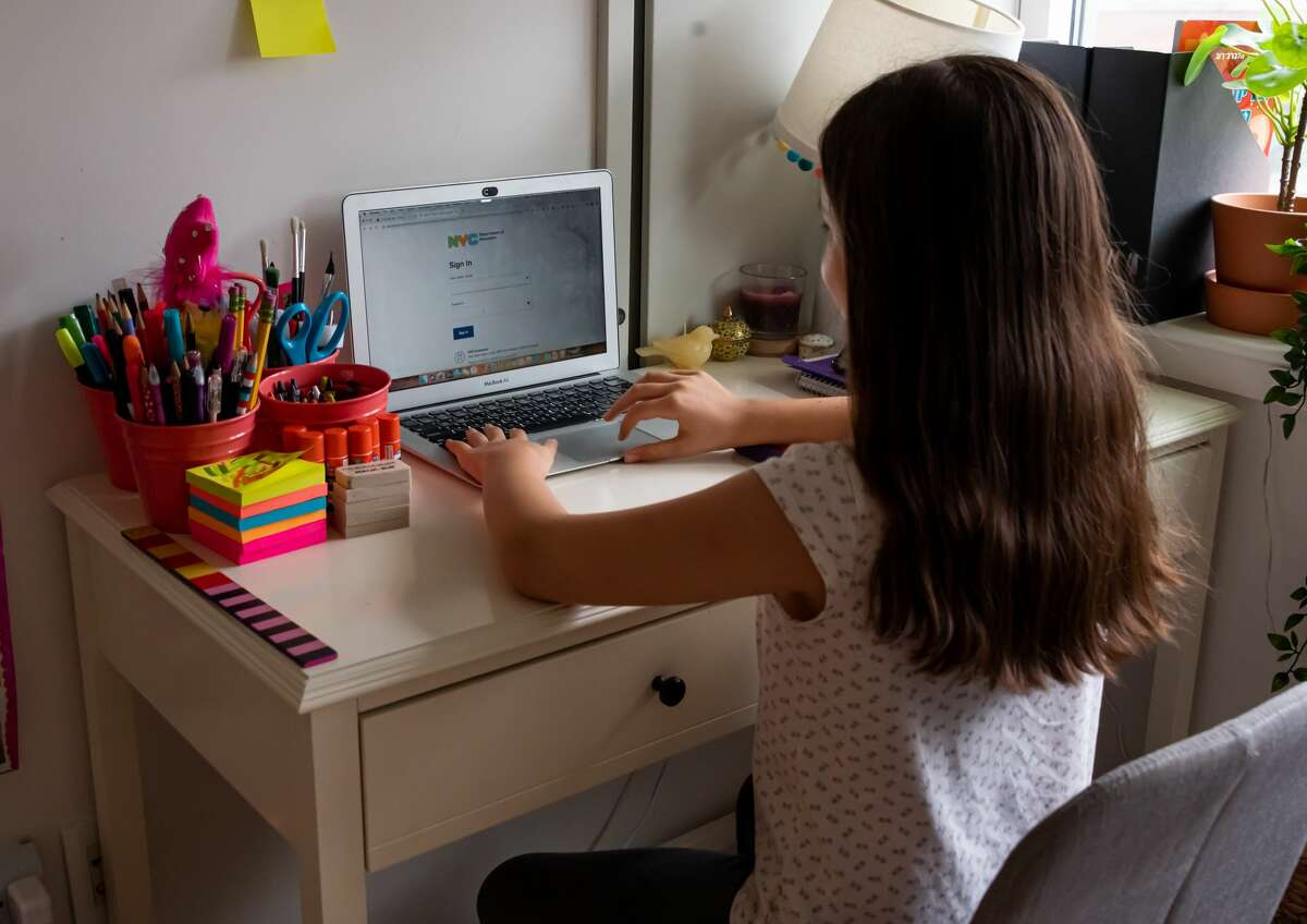 An elementary school student sits in front of her computer as she attends school remotely from her home in New York City on September 27, 2020 in New York City.