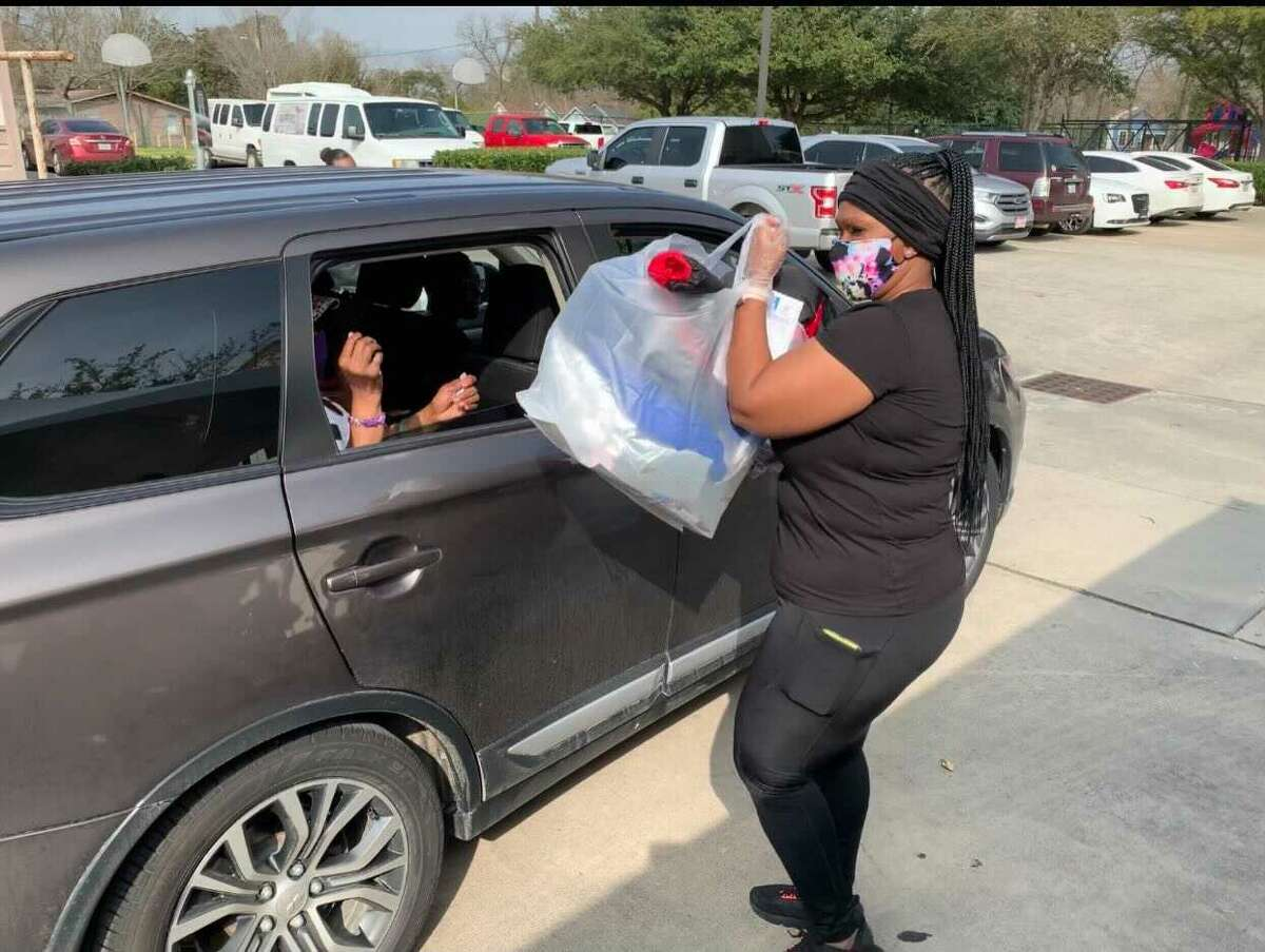 Volunteers are seen placing coats into cars during the Warm Wishes Coat Drive.