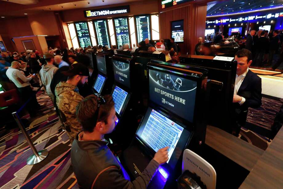 FILE - In this March 11, 2020, file photo, patrons place in person bets during the launch of legalized sports betting in Michigan at the MGM Grand Detroit casino in Detroit. (AP Photo/Paul Sancya, File) / Copyright 2020 The Associated Press. All rights reserved