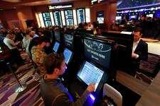FILE - In this March 11, 2020, file photo, patrons place in person bets during the launch of legalized sports betting in Michigan at the MGM Grand Detroit casino in Detroit. (AP Photo/Paul Sancya, File)
