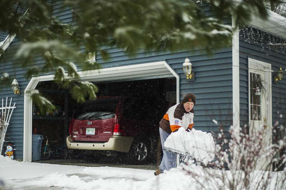 Midland resident Tim Coffey uses a shovel to clear his driveway of snow during a day of constant precipitation Tuesday, Jan. 26, 2021 in Midland. (Katy Kildee/kkildee@mdn.net) Photo: (Katy Kildee/kkildee@mdn.net)