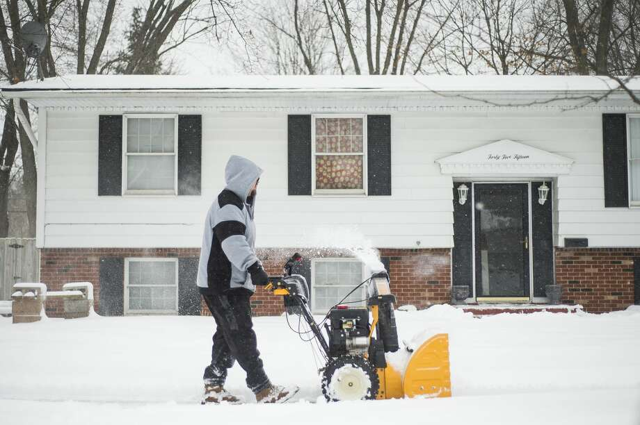 Midland residents use snowblowers and shovels to clear sidewalks and driveways during a day of constant precipitation Tuesday, Jan. 26, 2021 in Midland. (Katy Kildee/kkildee@mdn.net) Photo: (Katy Kildee/kkildee@mdn.net)