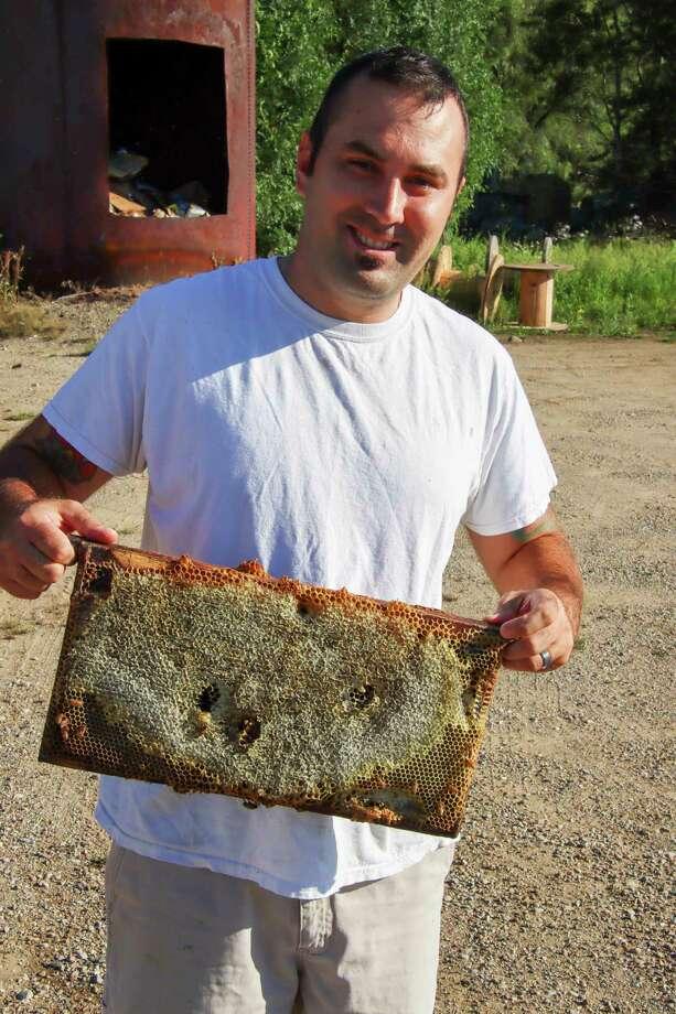 Brett McCoy holds up the 7-pound comb that is full of honey.