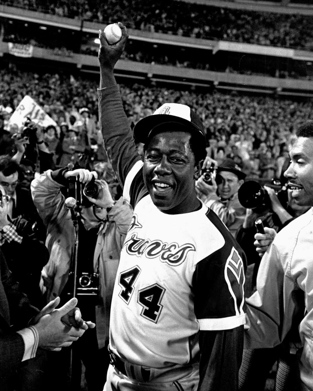 Hank Aaron holds a the ball he hit for his 715th career home run. Aaron transformed a chase for the most hallowed record in sports into a quest showcasing that the national pastime was as inextricably tied to the national problem of racism as is every American institution.