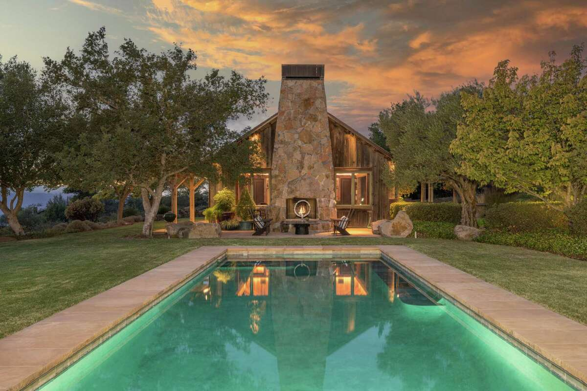 A sparkling pool stretches beside the St. Helena home.