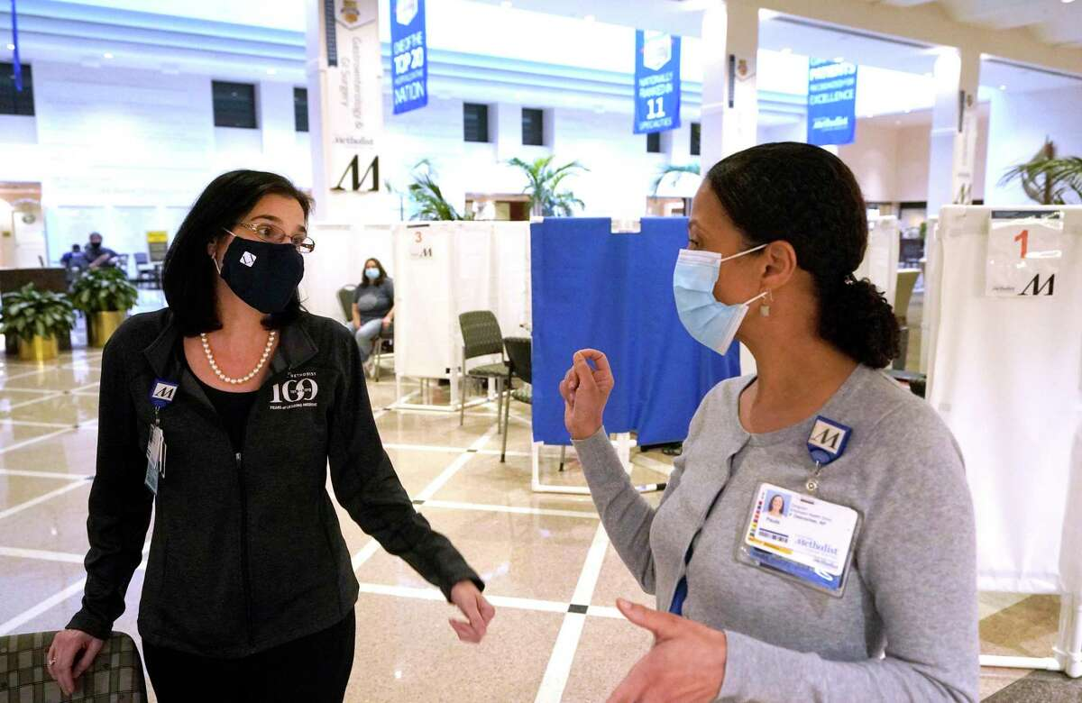 Roberta Schwartz, Houston Methodist Hospital CEO, left, talks with Paula DesRoches, director of employee health clinic, in the Crain Garden area that was being used for COVID-19 vaccinations for employees and first responders, Tuesday, Jan. 19, 2021 in Houston.