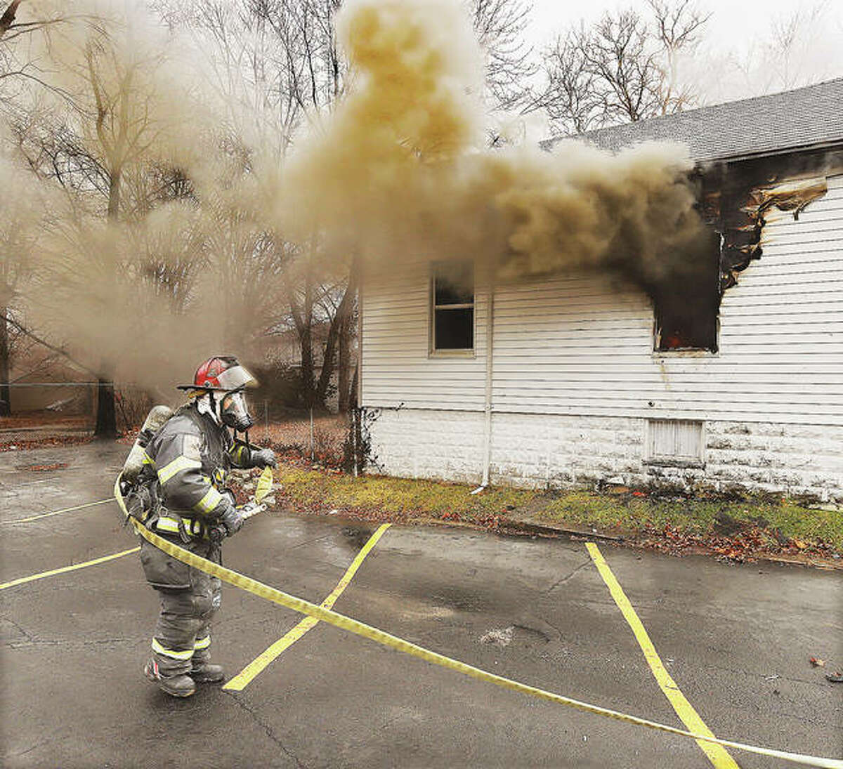 An Alton firefighter pulls a hose line into place at about 12:30 p.m. Tuesday at 1729 Main St., Alton during a fire that extensively damaged the home. Residents of the home escaped unharmed. Alton firefighters called the East Alton Fire Department for assistance. The cause of the fire is under investigation.