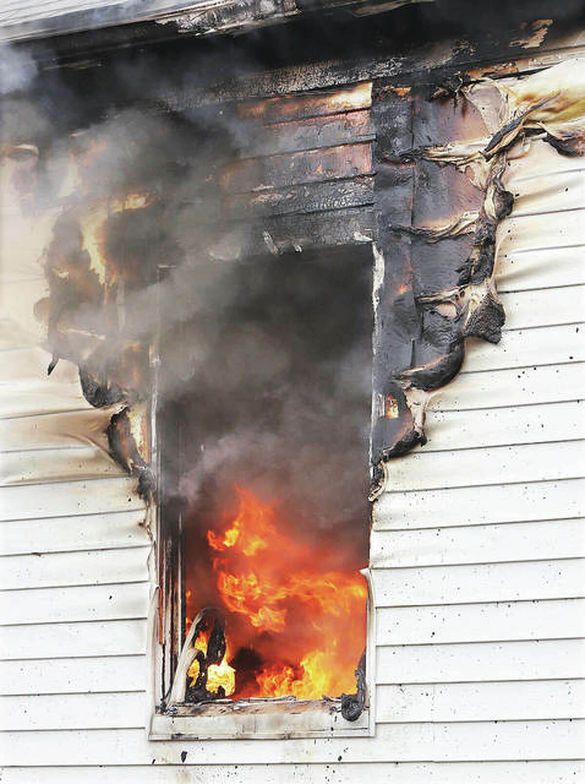 Flames can be seen roaring inside a room on the north side of the house Tuesday. No injuries were reported in the blaze.