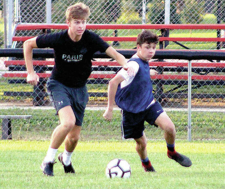 Sam Stutz, left, controls the ball during a summer 2018 workout during his playing days at Alton High. Stutz, after some two years off because of surgery and the pandemic, said he's more than ready to return to playing when NJCAA spring soccer starts in late March. At right is AHS players Evan Williams Photo: Pete Hayes | The Telegraph