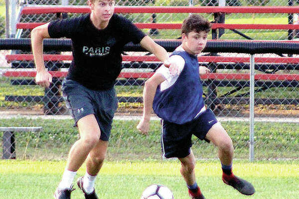 Sam Stutz, left, controls the ball during a summer 2018 workout during his playing days at Alton High. Stutz, after some two years off because of surgery and the pandemic, said he's more than ready to return to playing when NJCAA spring soccer starts in late March. At right is AHS players Evan Williams