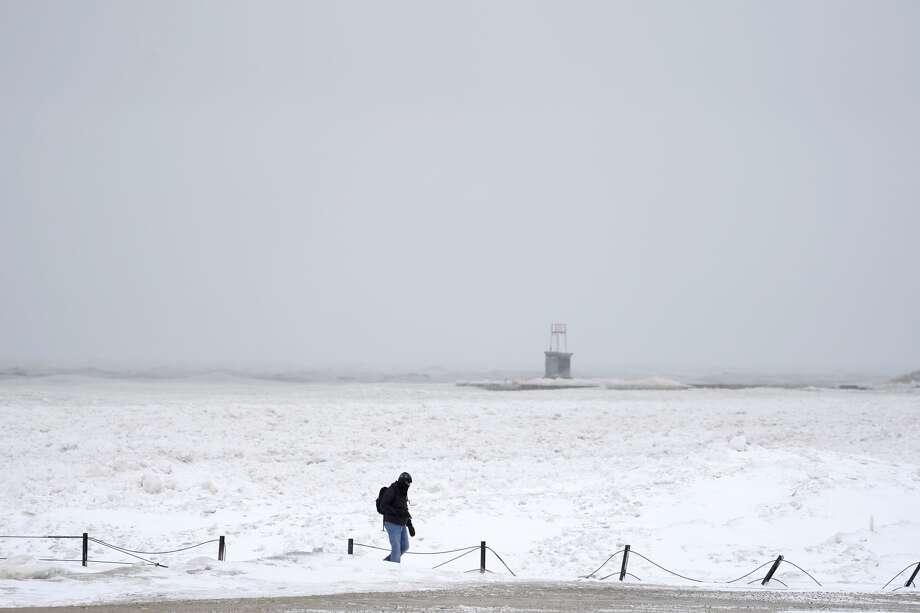 A lone man walks along a frozen section of North Ave. beach on Lake Michigan north of downtown Chicago Tuesday, Jan. 26, 2021. A major winter storm dumped more than a foot of snow on parts of the middle of the country stretching from central Kansas northeast to Chicago and southern Michigan.(AP Photo/Charles Rex Arbogast) Photo: Charles Rex Arbogast/AP / Copyright 2021 The Associated Press. All rights reserved