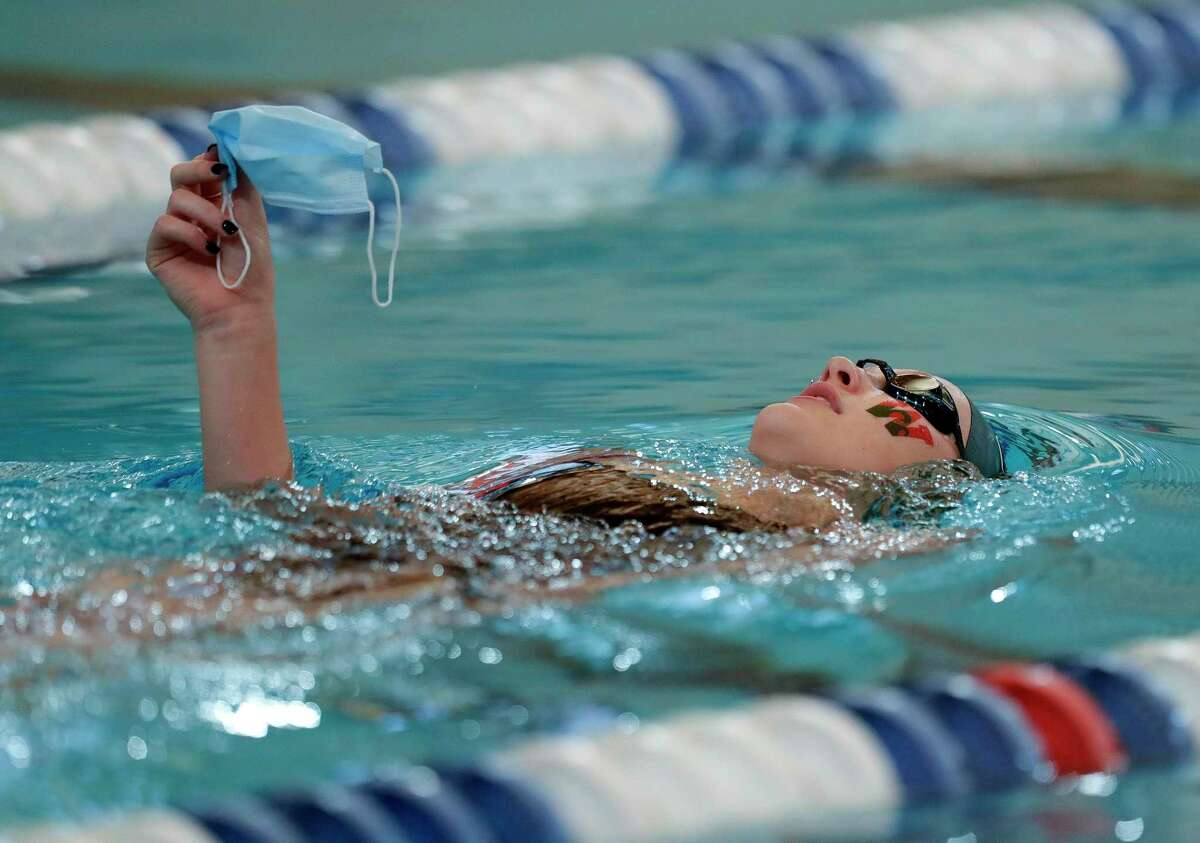 Alyssa Sorensen of The Woodlands holds her mask out of the water as she crosses from one side of the pool to the other before the District 13-6A swimming meet at the Conroe ISD Natatorium, Saturday, Jan. 23, 2021, in Shenandoah.